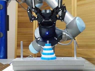 Industrial robot arm solving the Towers of Hanoi puzzle