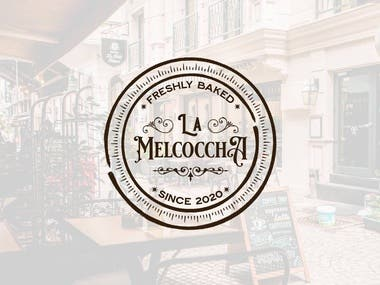 """La Melcoccha is a local bakery shop located in Medellin, Antioquia, Columbia. They bake delicious sweets like fudge brownies, cakes, and giant cookies.  The vision for this brand is to offer the finest of desserts to loyal customers, mostly sugar lovers looking for a pleasing experience. The logo had to convey a feel of premium quality and vintage style.  A challenging task was to figure out how to best position the words. We decided to put """"La"""" above """"Melchoccha"""" to make it more prominent because the last is means a thick, handmade candy in Columbian.  I designed an emblem and styled it like a royal stamp, keeping in mind people who seek premium-quality sweets. To accomplish that, I used a Royal Signage, serif font, and enhanced the effect with a few ornaments.  I aimed to keep a balance between the royal feel and the modern look of the design. Both the client and I chose a simple pattern for the outline of the emblem, so it looks more contemporary."""